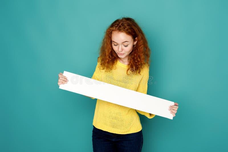 Jeune femme tenant la bannière blanche vide images stock