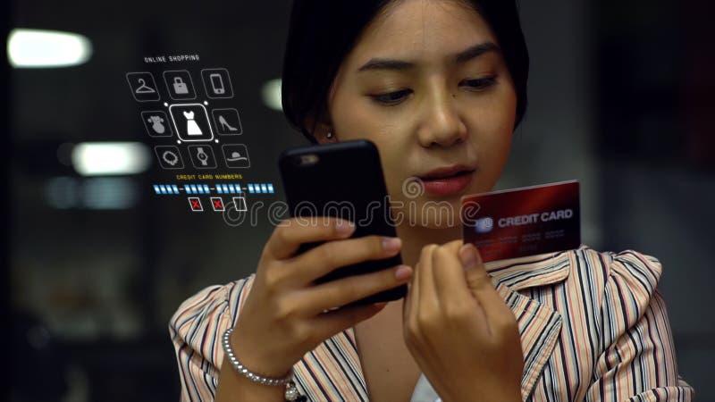 Jeune femme tenant la carte de crédit et le téléphone photos libres de droits