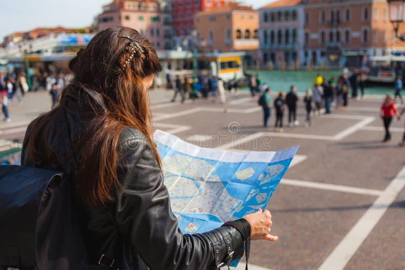Jeune femme tenant la carte de papier de Venise le jour ensoleillé, beaucoup de touristes sur le fond images stock
