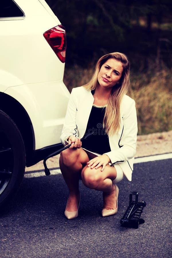Jeune femme tenant la clé de jacke et de roue image libre de droits