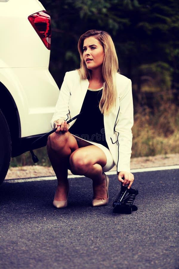 Jeune femme tenant la clé de jacke et de roue photographie stock libre de droits