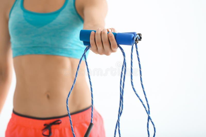 Jeune femme tenant la corde à sauter sur le fond photo stock