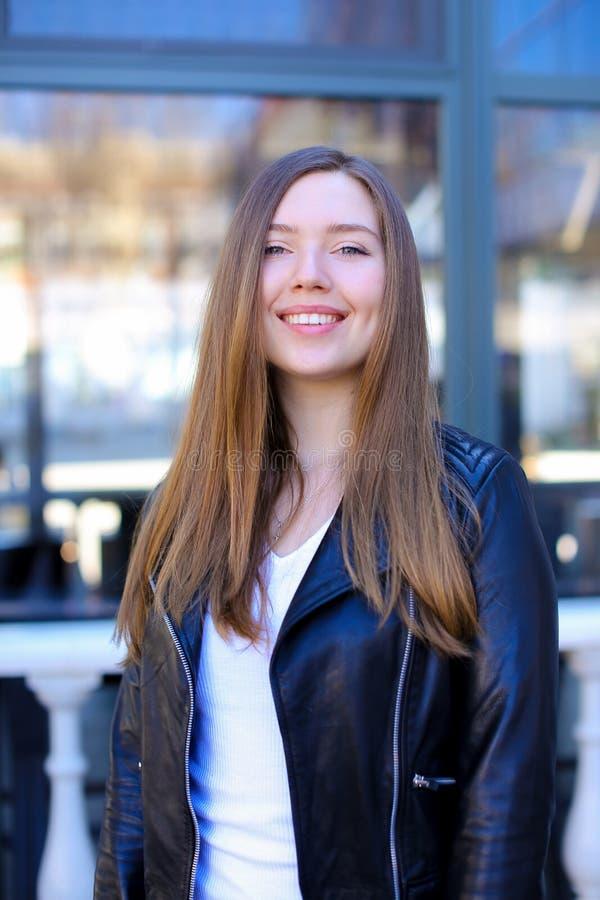 Jeune femme tenant la fenêtre proche dans la ville photo stock