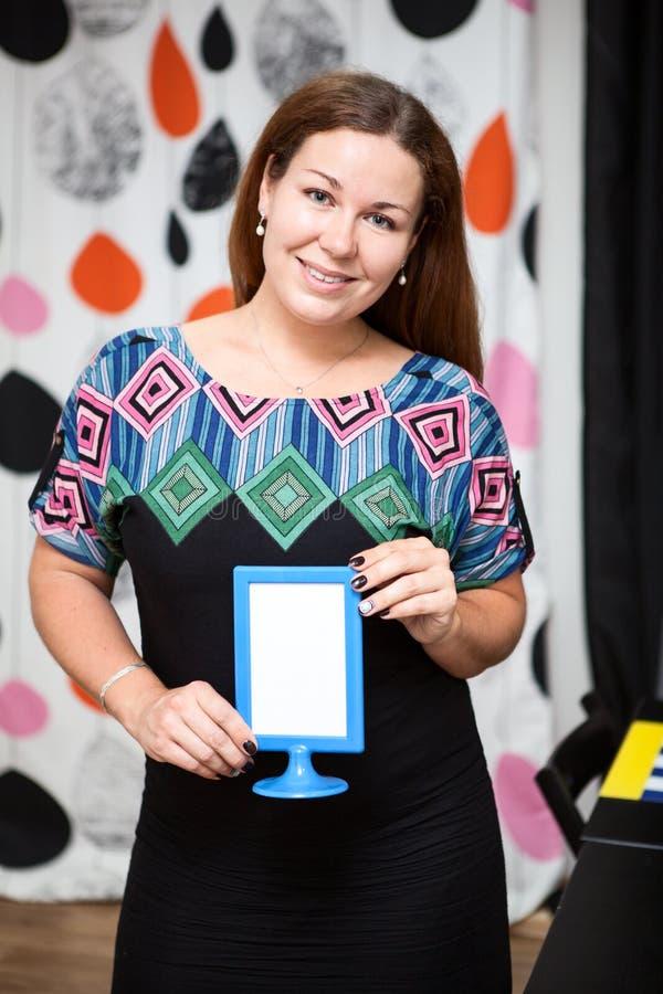 Jeune femme tenant la feuille de papier blanche dans le cadre image stock