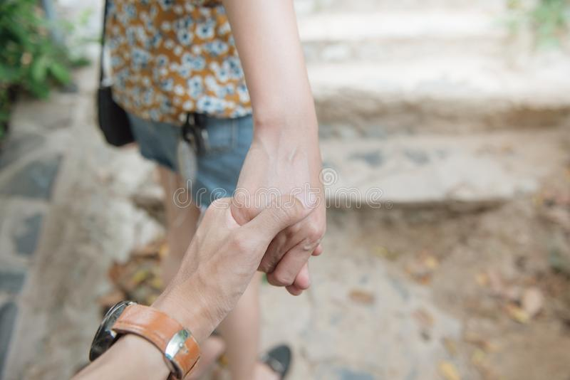 Jeune femme tenant la main du ` s d'homme et le menant sur le fond en pierre d'étape photographie stock libre de droits