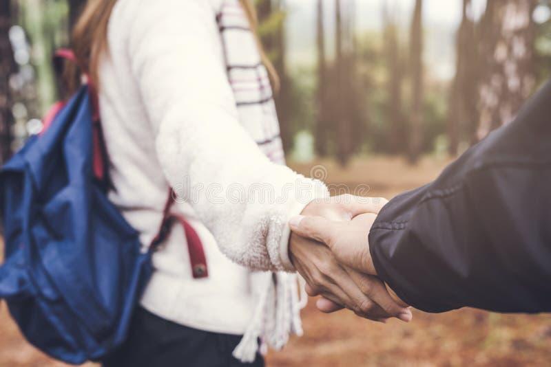 Jeune femme tenant la main du ` s d'homme et le menant sur la nature photo stock
