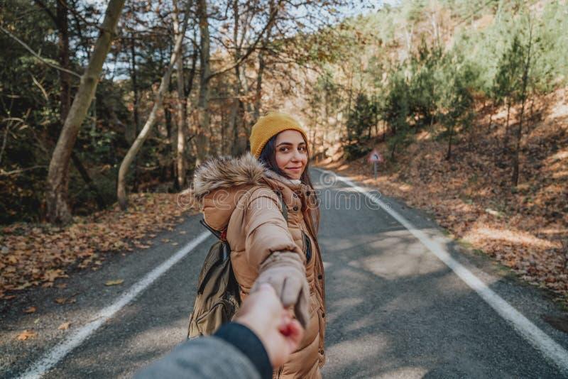 Jeune femme tenant la main du ` s d'homme et le menant sur la nature Couples dans l'amour images libres de droits