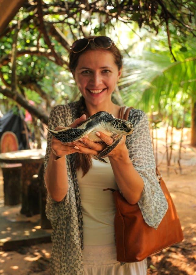 Jeune femme tenant la tortue dans des ses mains Le CEN d'établissement d'incubation de tortue de mer image libre de droits