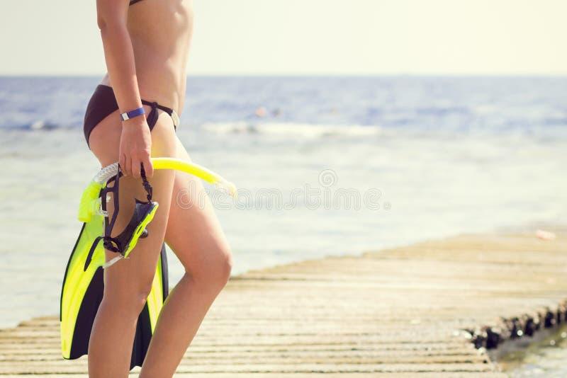 Jeune femme tenant la vitesse naviguante au schnorchel regardant la mer image libre de droits