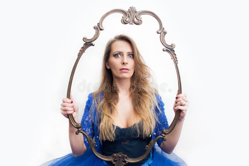 Jeune femme tenant le cadre décoratif photographie stock libre de droits