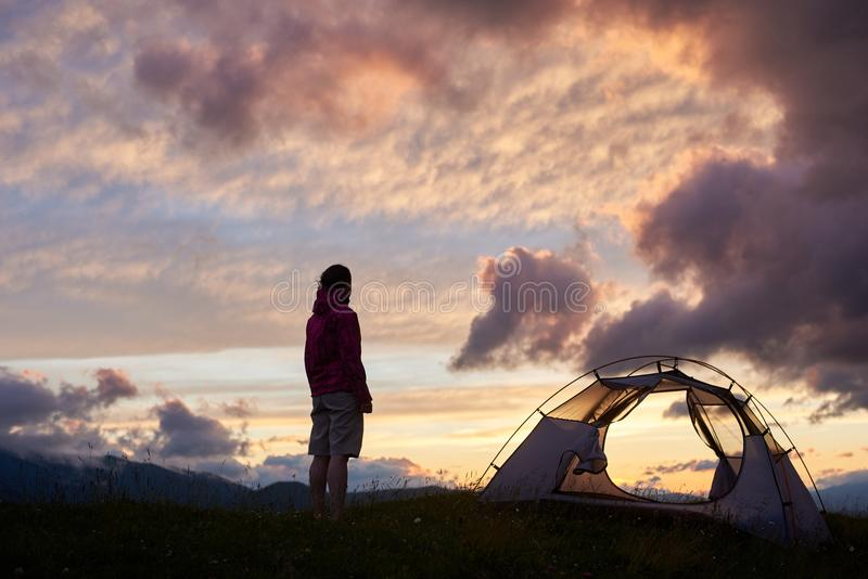 Jeune femme tenant le camp proche, beau coucher du soleil de nature sur la montagne image stock