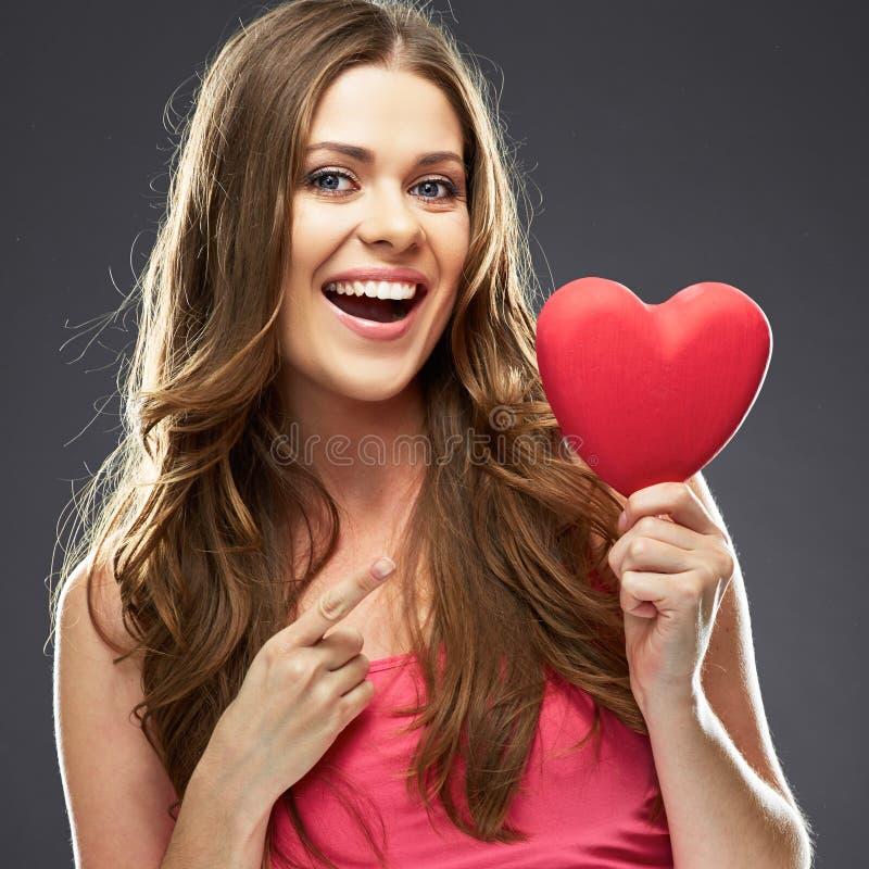 Jeune femme tenant le coeur et l'indication par les doigts image libre de droits