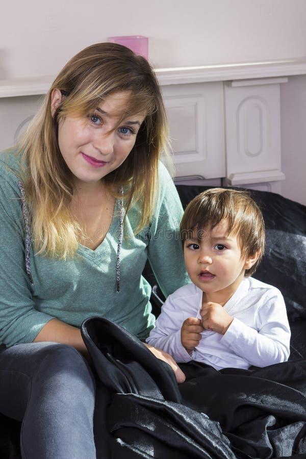 Jeune femme tenant le fils sur des bras photographie stock libre de droits