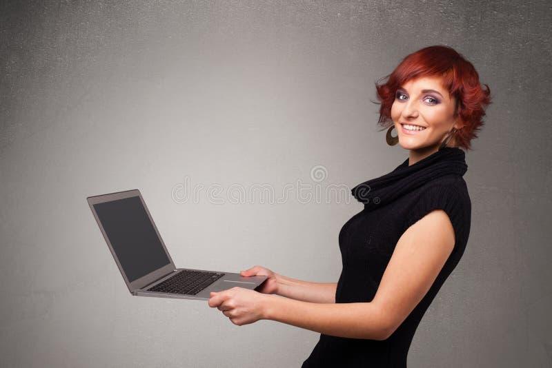Jeune femme tenant le laptot moderne photographie stock