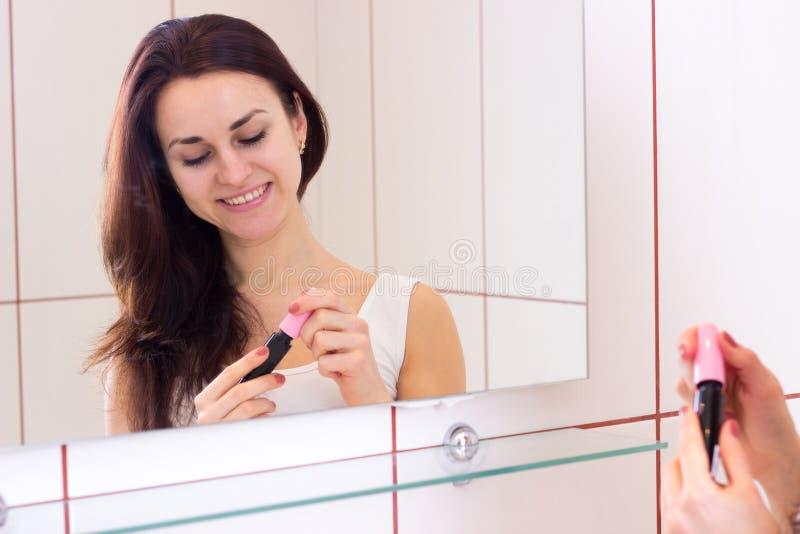 Jeune femme tenant le mascara dans la salle de bains photos libres de droits
