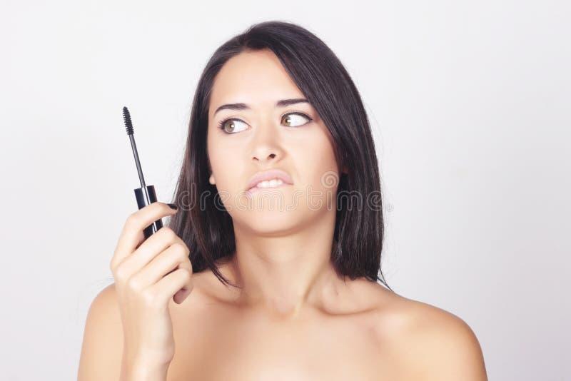 Jeune femme tenant le mascara pour ses cils images stock