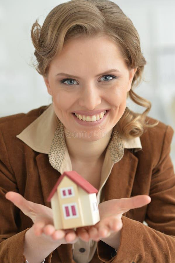 Jeune femme tenant le modèle de la maison dans le bureau images libres de droits