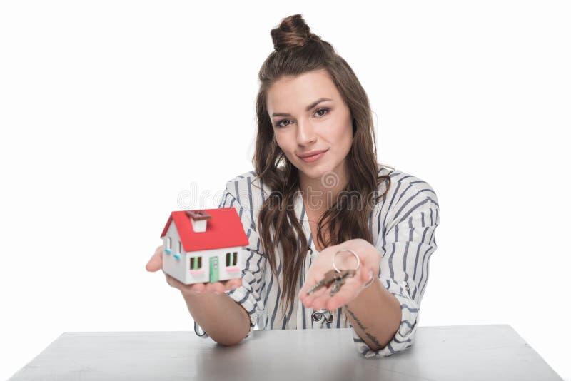 Jeune femme tenant le modèle de maison avec des clés et souriant à l'appareil-photo image libre de droits