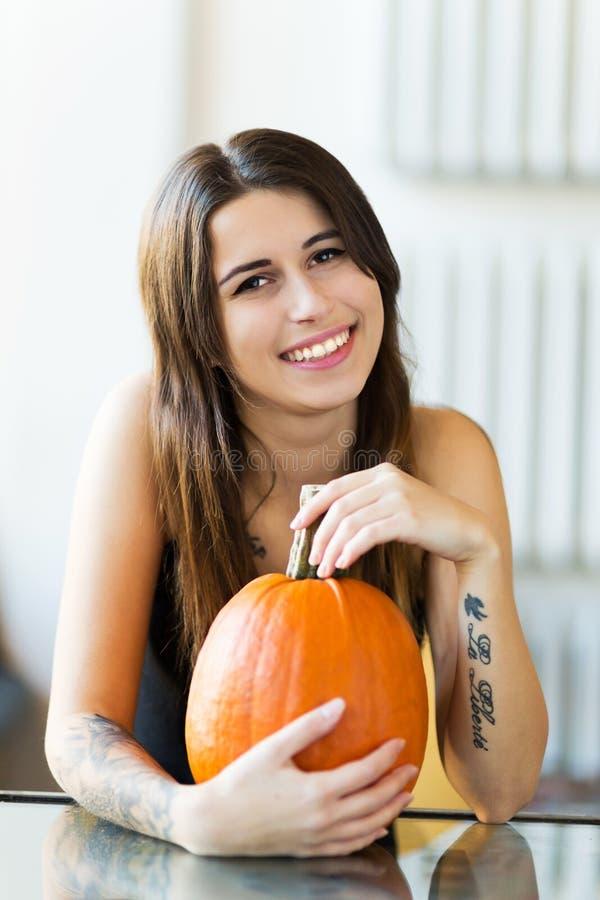 Jeune femme tenant le potiron photos stock