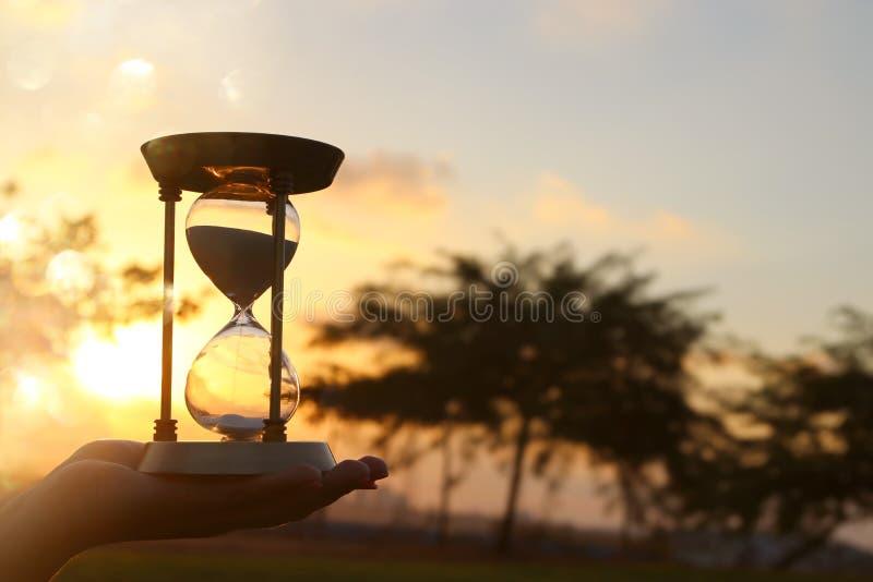 Jeune femme tenant le sablier pendant le coucher du soleil Type de cru image libre de droits