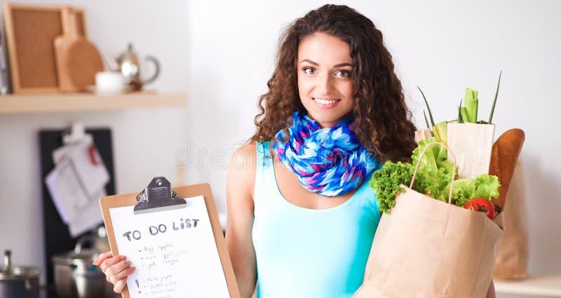 Jeune femme tenant le sac d'épicerie avec des légumes Position dans la cuisine images libres de droits