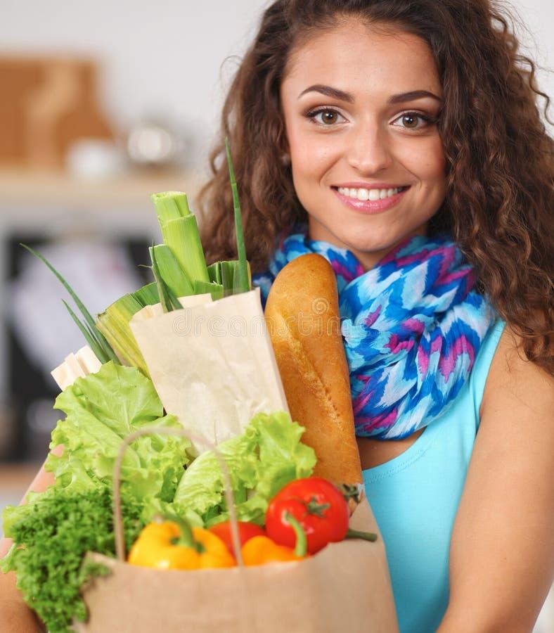 Download Jeune Femme Tenant Le Sac D'épicerie Avec Des Légumes Se Tenant Dans La Cuisine Image stock - Image du laitue, vert: 87700689