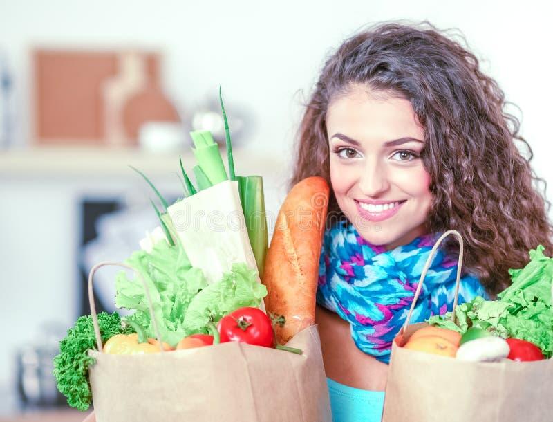 Download Jeune Femme Tenant Le Sac D'épicerie Avec Des Légumes Se Tenant Dans La Cuisine Image stock - Image du beau, heureux: 87700693