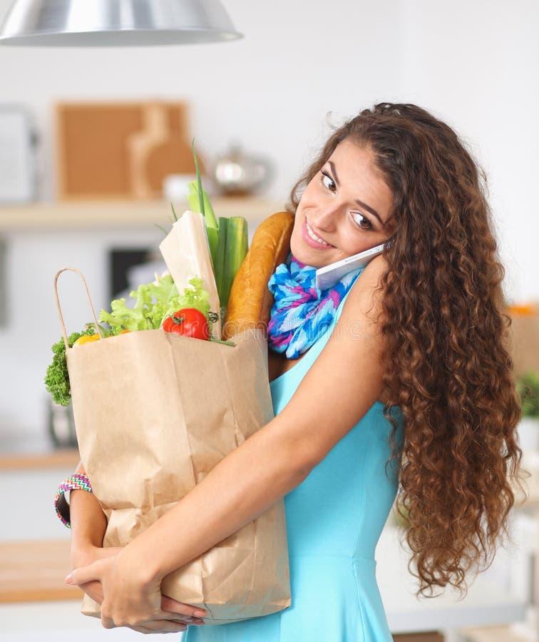 Download Jeune Femme Tenant Le Sac D'épicerie Avec Des Légumes Se Tenant Dans La Cuisine Photo stock - Image du heap, beauté: 87700696