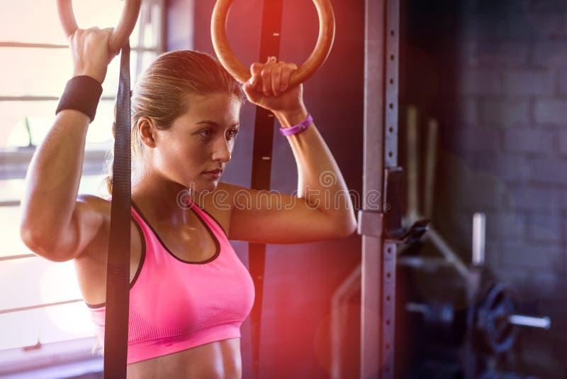 Jeune femme tenant les anneaux gymnastiques dans le gymnase photos libres de droits