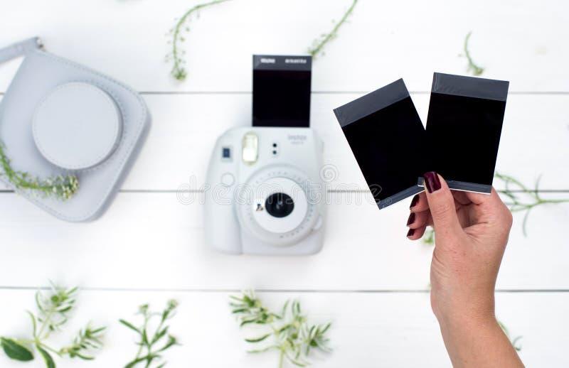 Jeune femme tenant les photos disponibles de cru Cadre de Palaroid Configuration plate photo stock