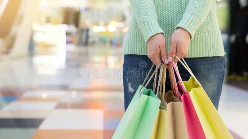 Jeune femme tenant les sacs à provisions colorés dans le centre commercial photos stock