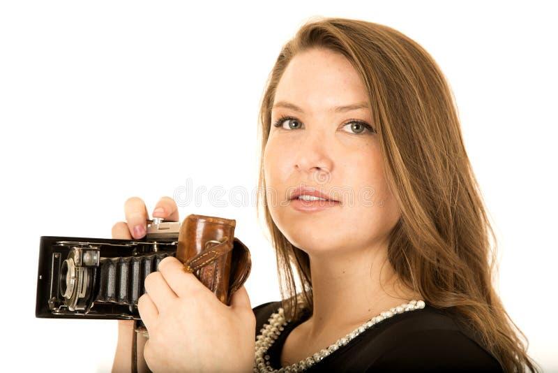 Jeune femme tenant un appareil-photo antique avec une expression sérieuse images stock