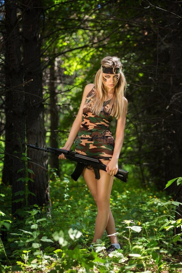 Jeune femme tenant un fusil d'assaut automatique photos stock