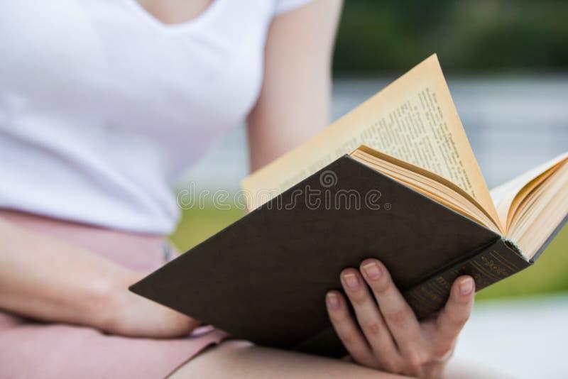 Jeune femme tenant un vieux livre dans des ses mains dehors photo libre de droits