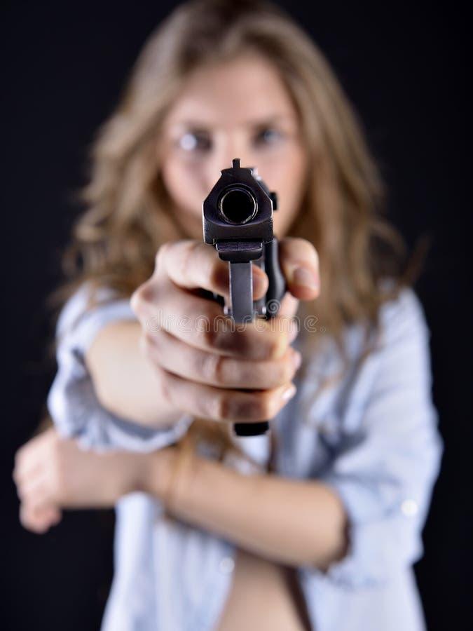 Jeune femme tenant une arme à feu images stock