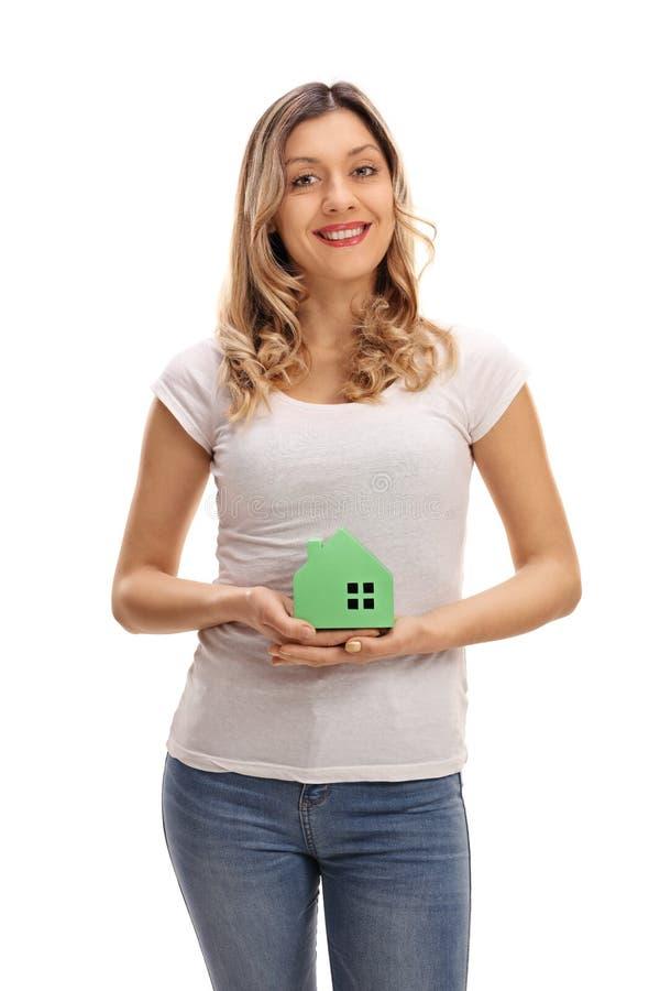 Jeune femme tenant une maison modèle images stock