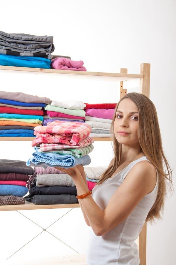 Jeune femme tenant une pile des vêtements image libre de droits