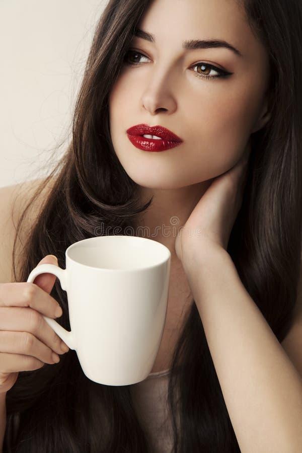 Jeune femme tenant une tasse blanche images stock