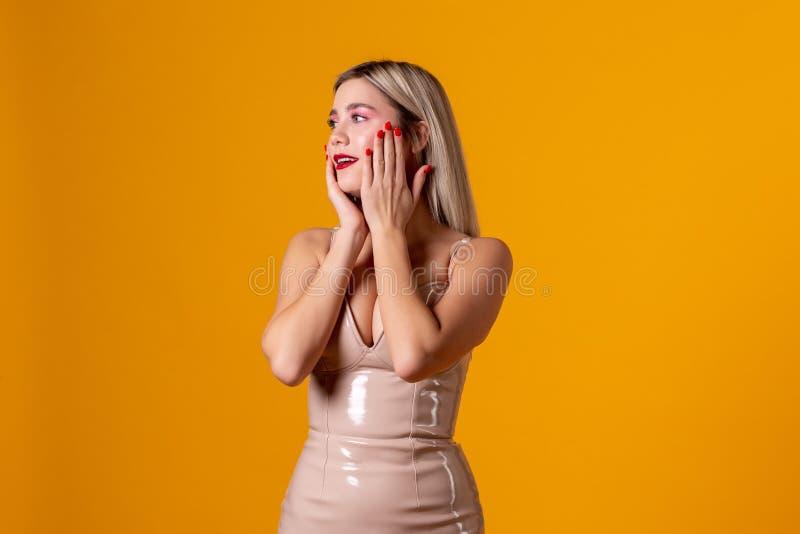 Jeune femme timide avec les cheveux blonds avec le maquillage à la mode touchant son visage image stock