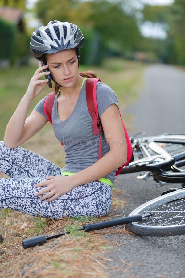 Jeune femme tombée vers le bas de la bicyclette réclamant l'aide photo libre de droits