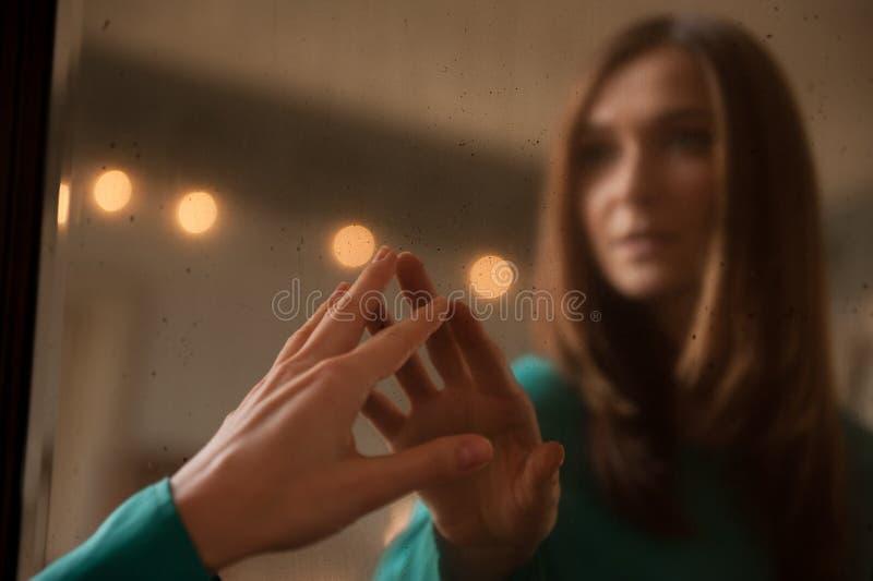 Jeune femme touchant sa propre réflexion dans un miroir photos stock