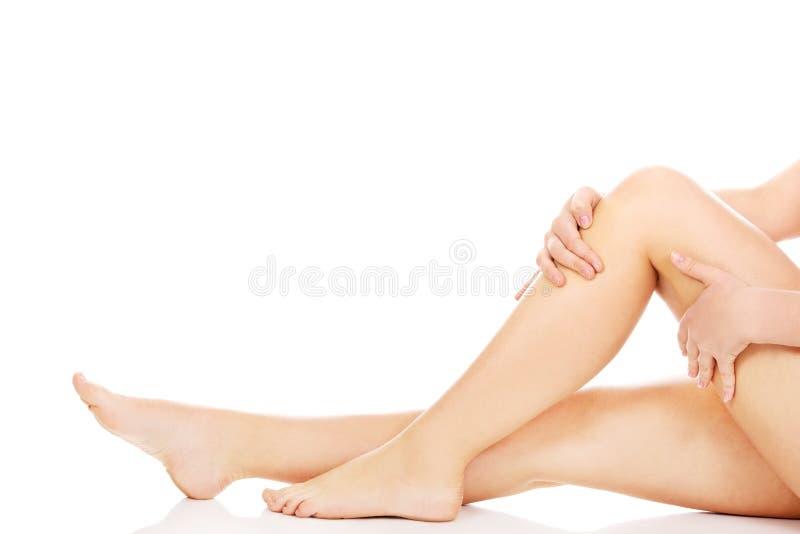 Jeune femme touchant ses jambes photo stock