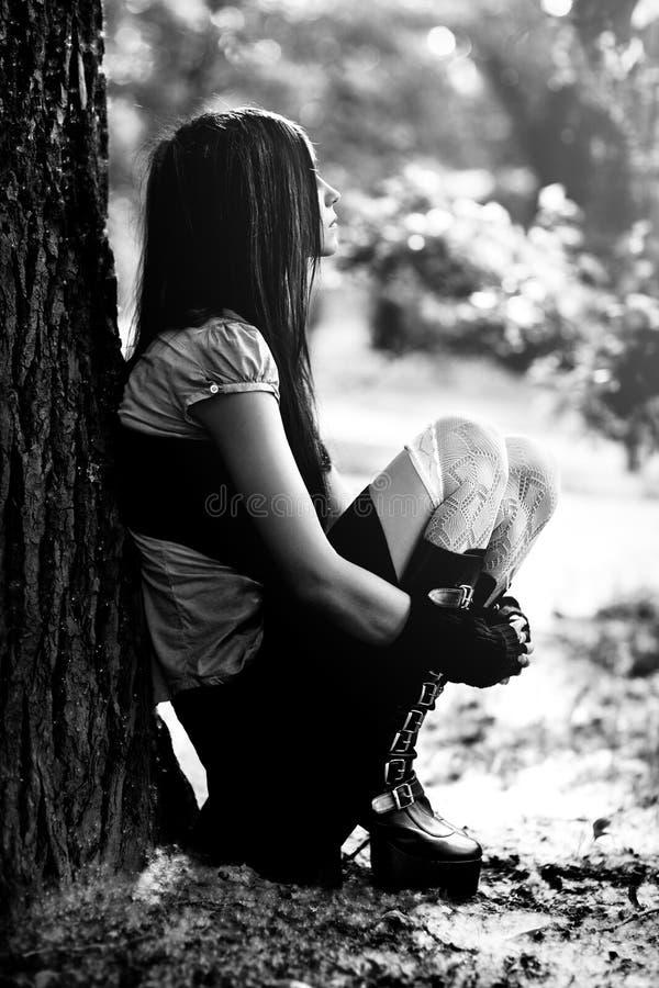 Jeune femme toughtful s'asseyant en stationnement images libres de droits