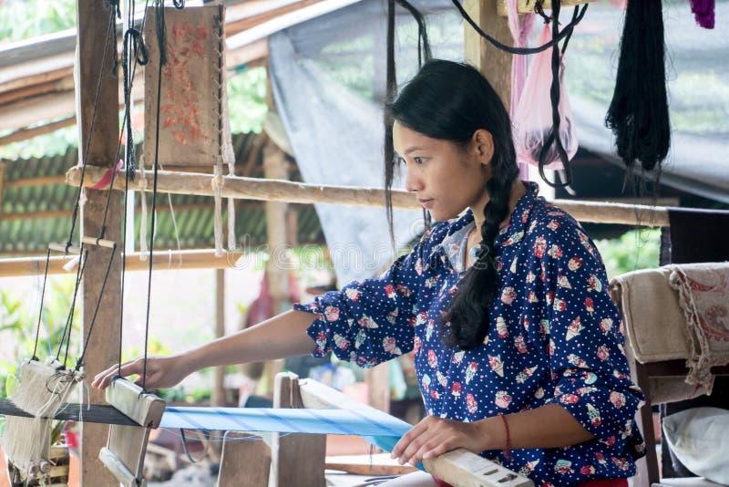 Jeune femme travaillant à la maison sur un métier à tisser de tissage photographie stock