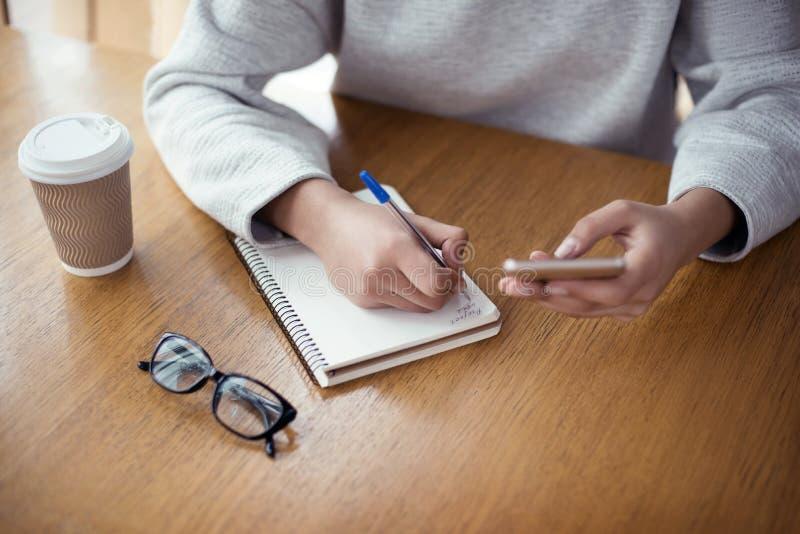 Jeune femme travaillant au bureau élégant créatif se reposant tenant s photo stock