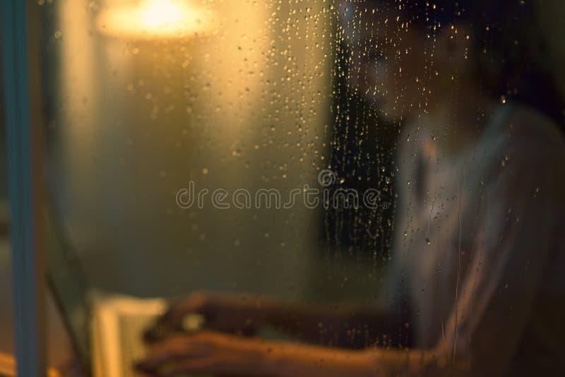 Jeune femme travaillant avec un ordinateur portable à côté d'une fenêtre image stock