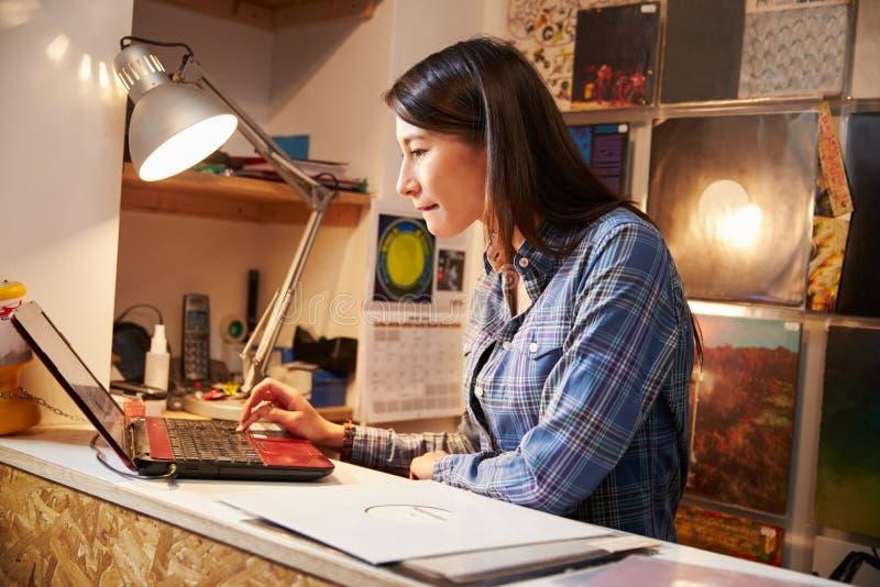 Jeune femme travaillant derrière le compteur à une boutique record photographie stock libre de droits