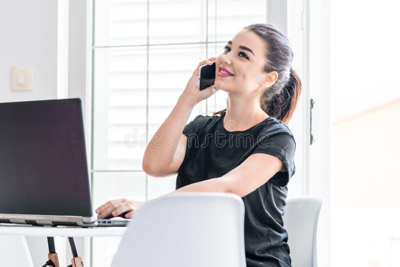 Jeune femme travaillant sur l'ordinateur portable et parlant par le téléphone portable en appartements lumineux image libre de droits