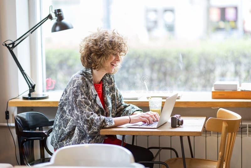 Jeune femme travaillant sur son ordinateur portable en café photo stock