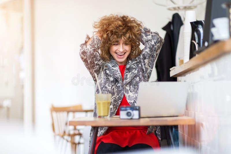 Jeune femme travaillant sur son ordinateur portable en café images libres de droits